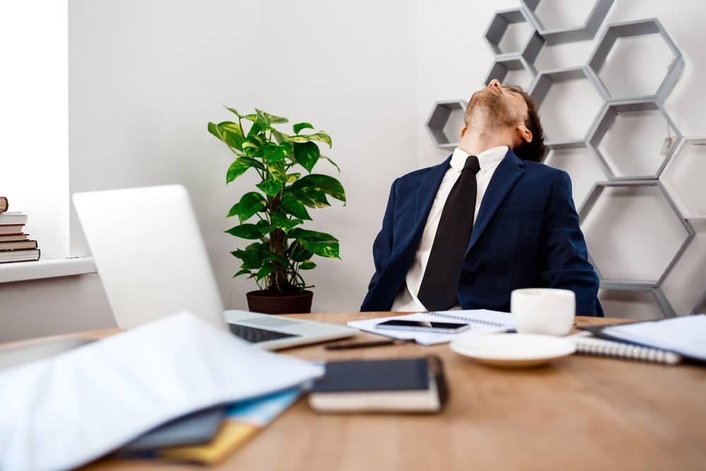 年轻疲惫的商人坐在工作场所有办公室背景_7855249
