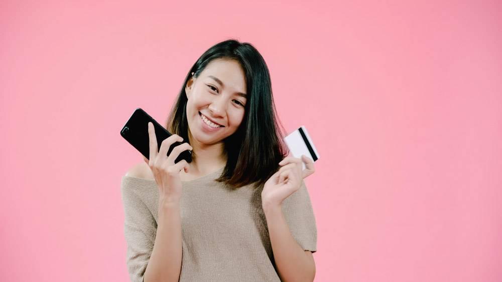 年轻的亚洲女子用智能手机刷卡网购感觉很_4395054
