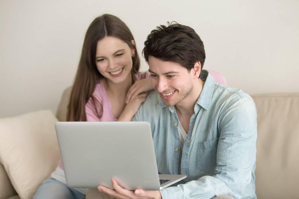年轻的幸福夫妇坐在那里使用笔记本电脑_3955515