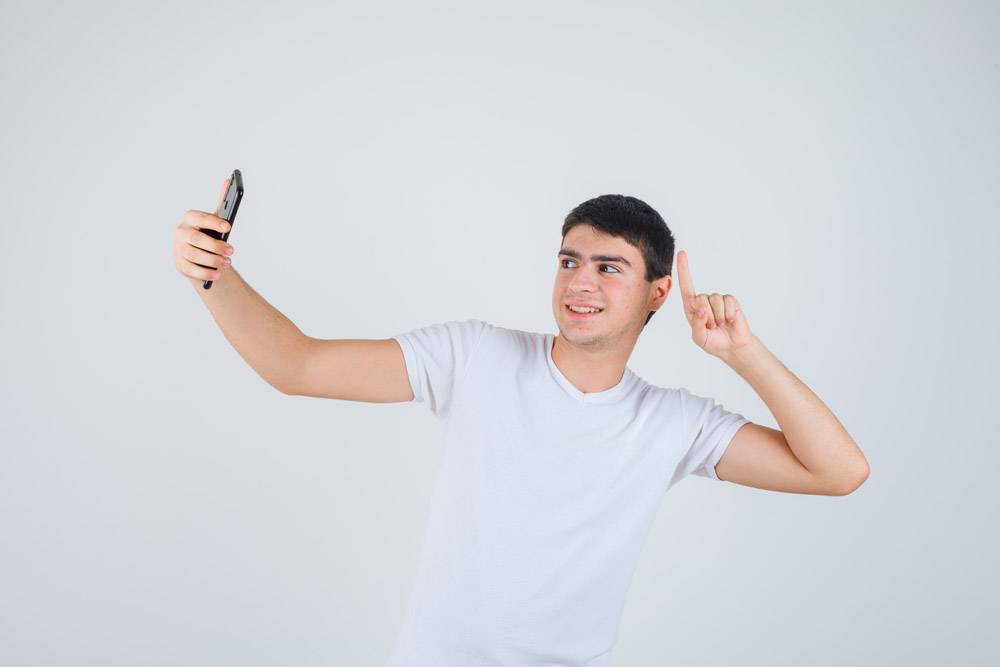 年轻的男性穿着t恤指着上边自拍看起来很_13463212