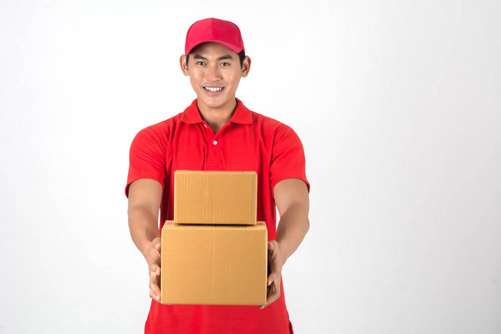 年轻英俊的送货员白底隔开盒子_1602586