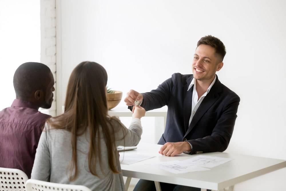 幸福的跨种族夫妇从房地产经纪人那里拿到新_3939781