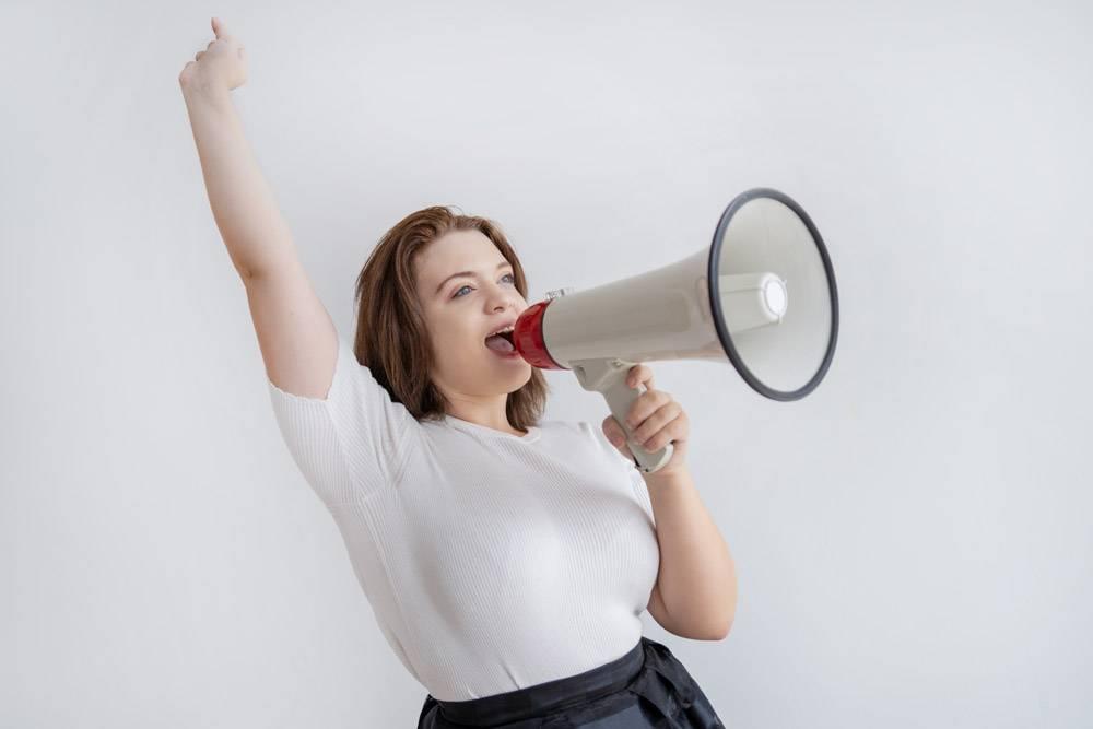 开心兴奋的年轻女子在扩音器里举起手臂尖叫_3583434