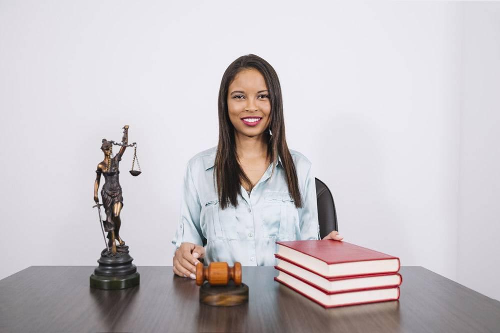 开朗的非洲裔美国妇女拿着木槌书籍和雕像_3741129