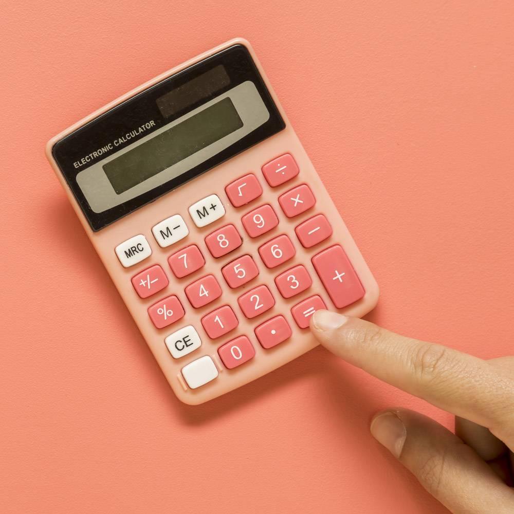 彩色表面上有粉红色计算器的手_4753032