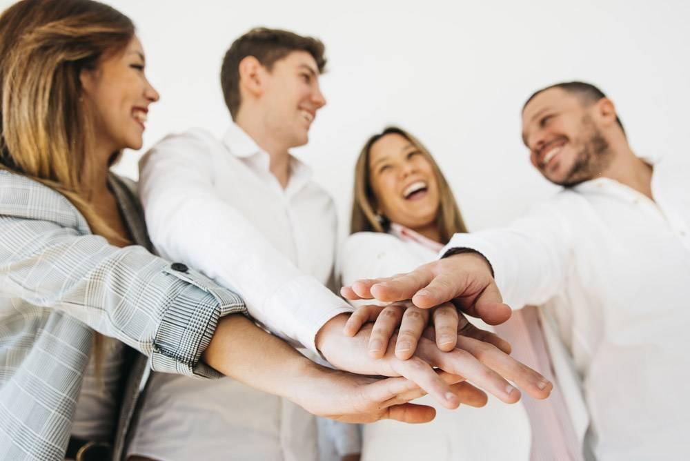 微笑的办公室同事把手放在一起_4989630