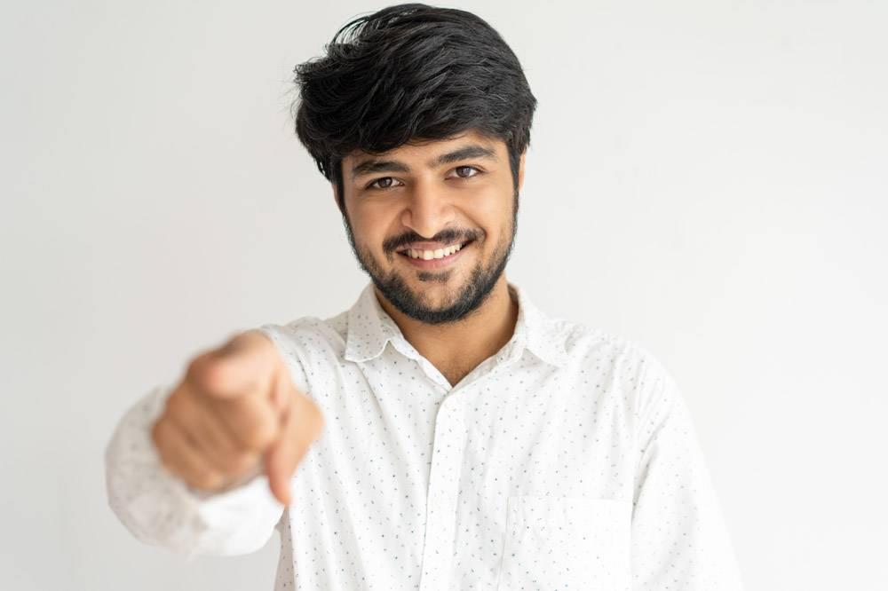 微笑的印度年轻男子指着你看着相机_4010434