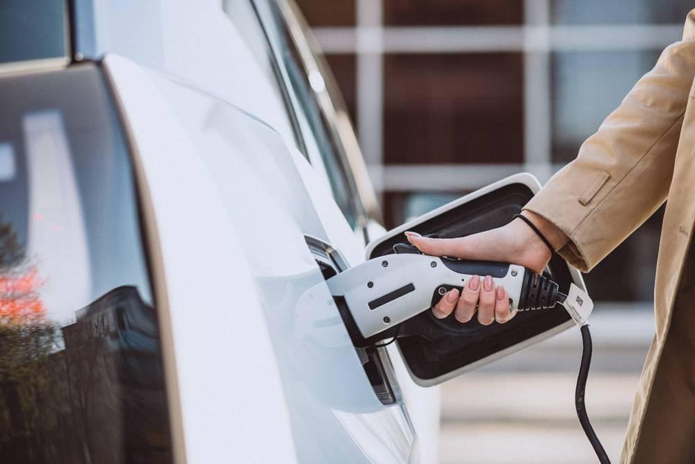 在电动加油站给电动车充电的女子_4757445