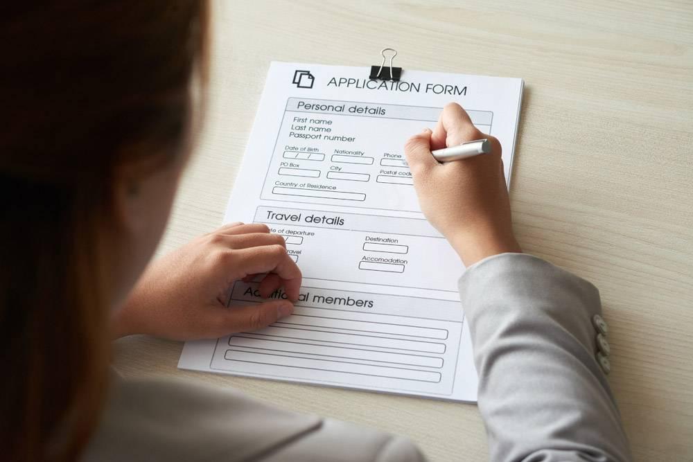 在肩上拍摄的匿名女子填写申请表的照片_5698751