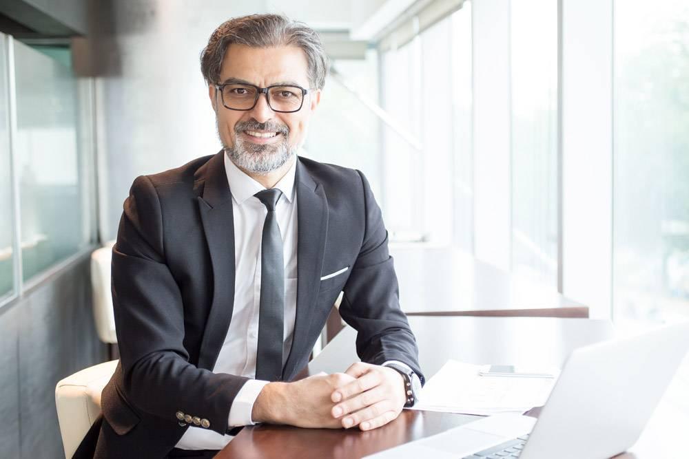坐在办公桌前微笑的商界领袖_1305400