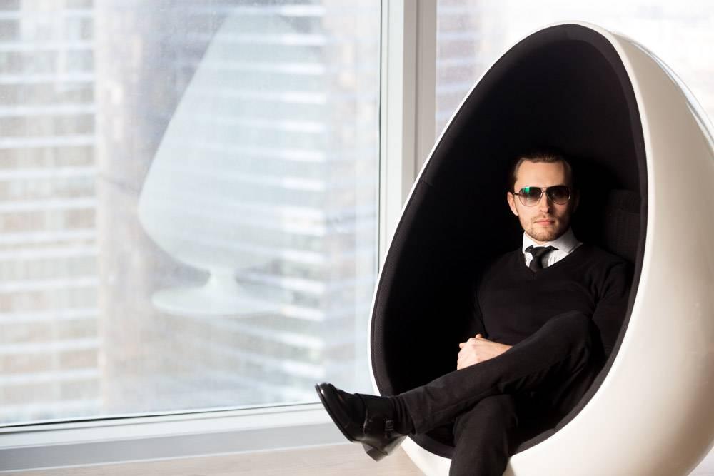 坐在未来主义蛋椅上的时尚神秘男子的肖像_4013412