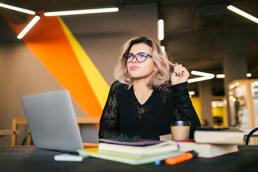 合办办公室里年轻漂亮女子穿着黑色衬衫坐_9405598