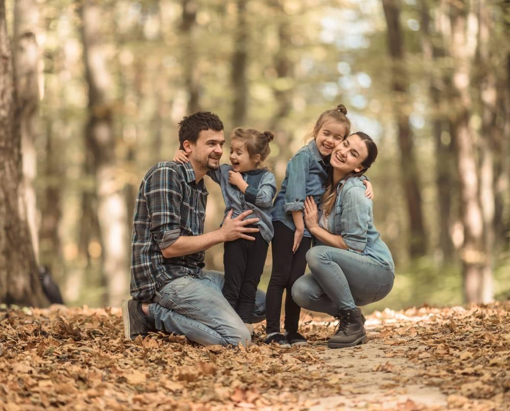 一个年轻的家庭带着孩子在秋天的森林里散步_8945827