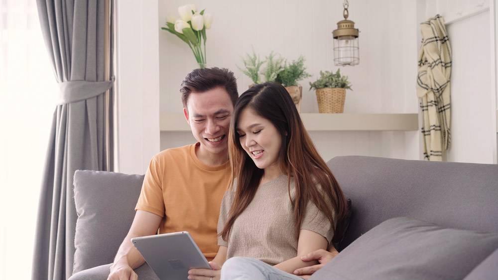 亚洲夫妇在家起居室使用平板电脑上网购物_4014658