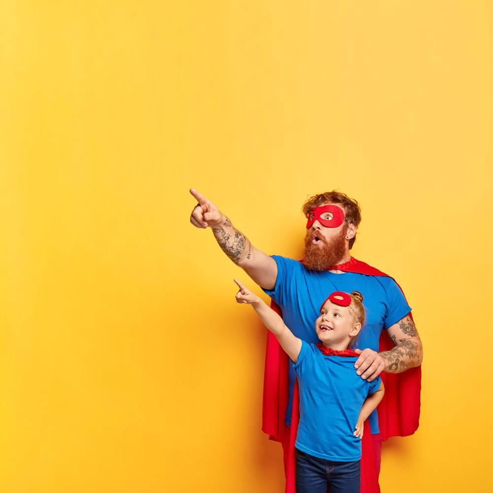 身着戏服的家庭超级英雄们带着兴趣和惊讶的_12349869