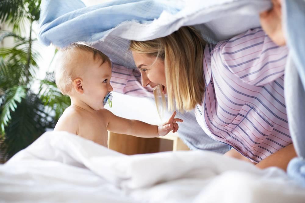 身着睡衣的迷人快乐的年轻女子与蹒跚学步的_11193336