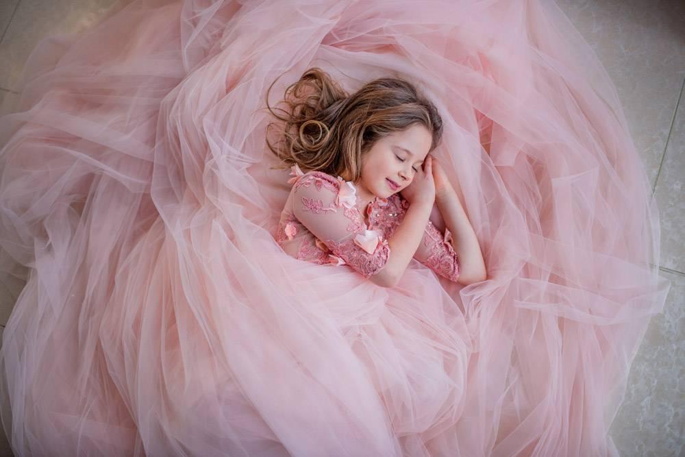 穿着粉色连衣裙的迷人小女孩睡在地板上看起_2612724