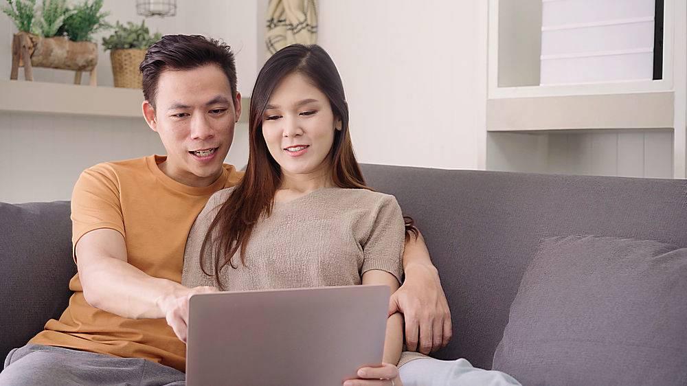 一对亚洲夫妇在家中的起居室里使用笔记本电_4014649