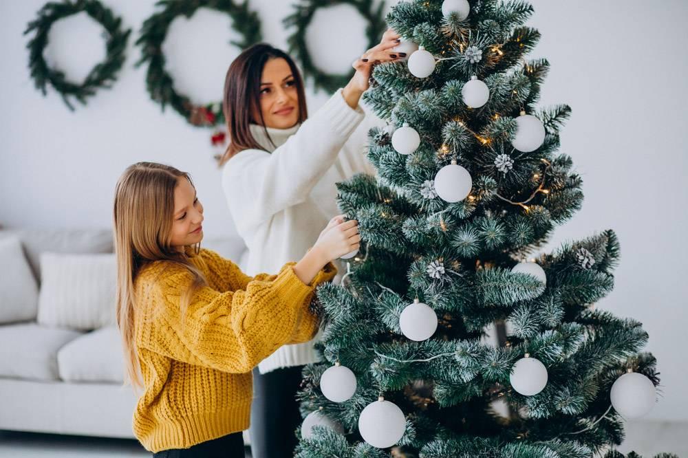 母亲带着女儿装饰圣诞树_12177320