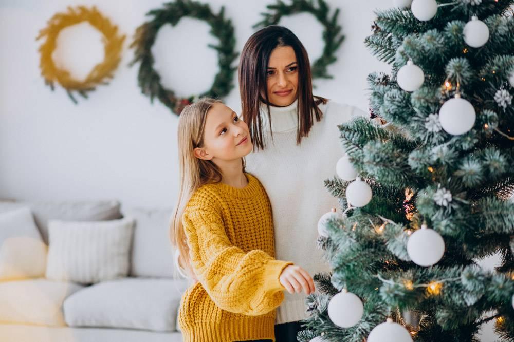 母亲带着女儿装饰圣诞树_12177329