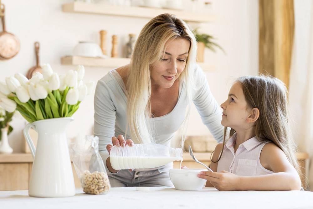 母亲把牛奶倒在女儿的麦片上的前景_10604637