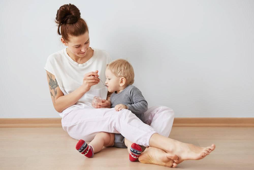 母亲用勺子喂她的男婴_10324075