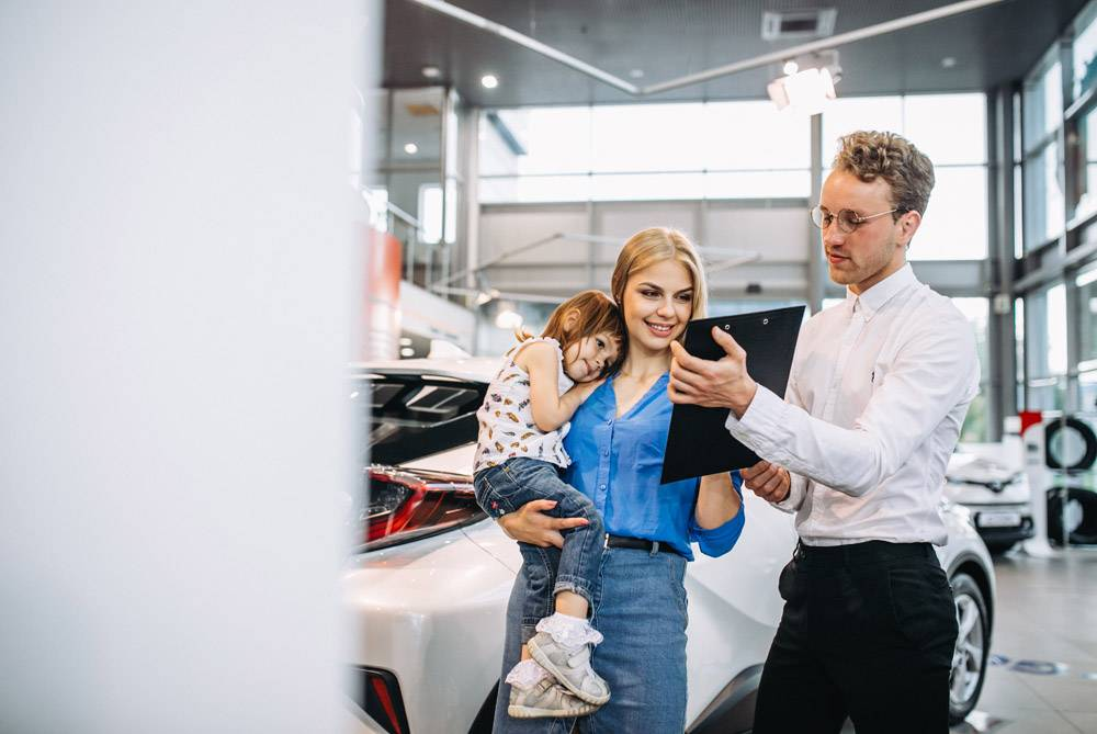 母女在汽车展厅与销售人员交谈_5157794