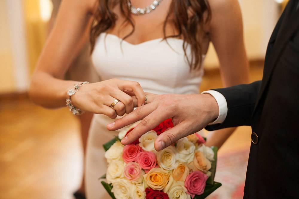 新娘把戒指戴在新郎的手指上放在鲜艳的婚_1234536