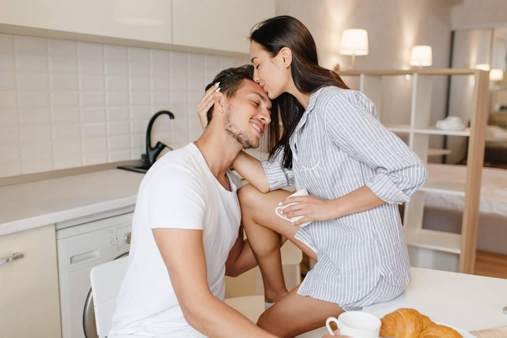 晒得黝黑的女人穿着男衫坐在桌子上亲吻丈_10785916