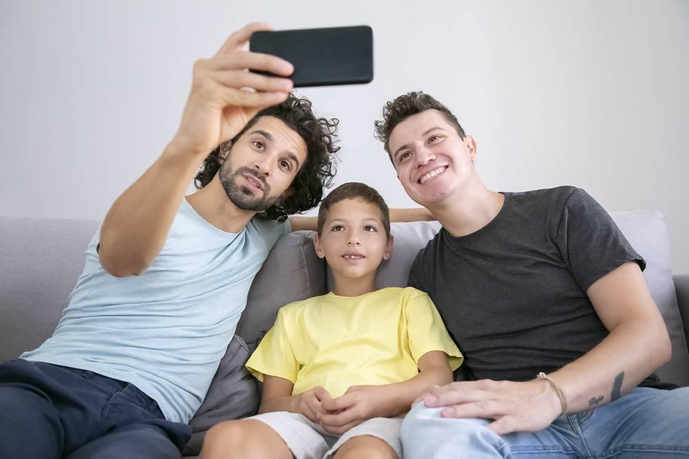 欢快的同性恋父母和孩子在牢房里自拍坐在_11293721