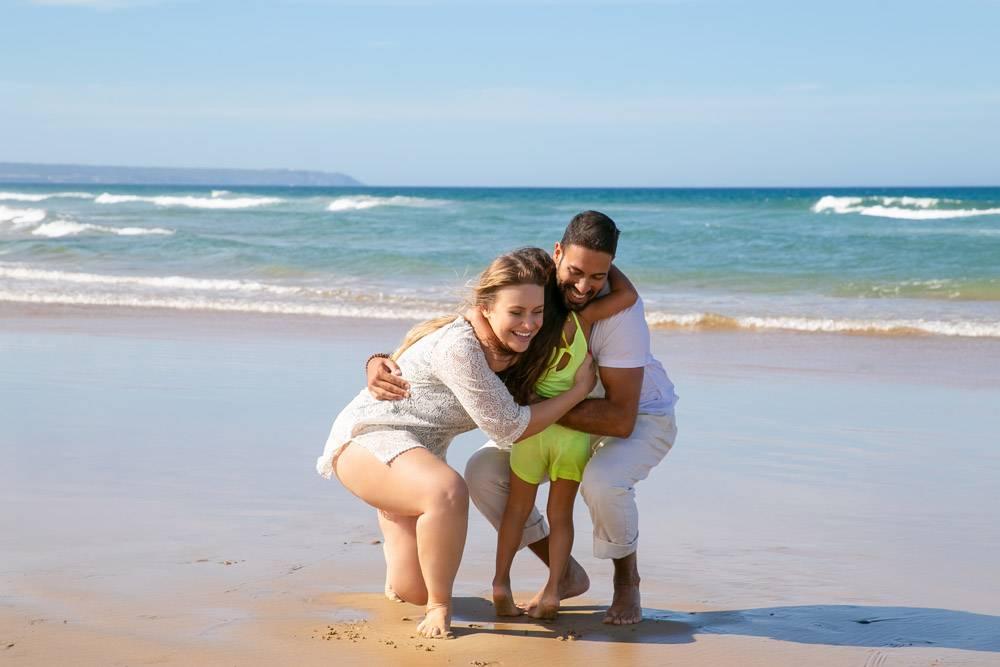欢快的年轻父母拥抱着小女儿_10586120