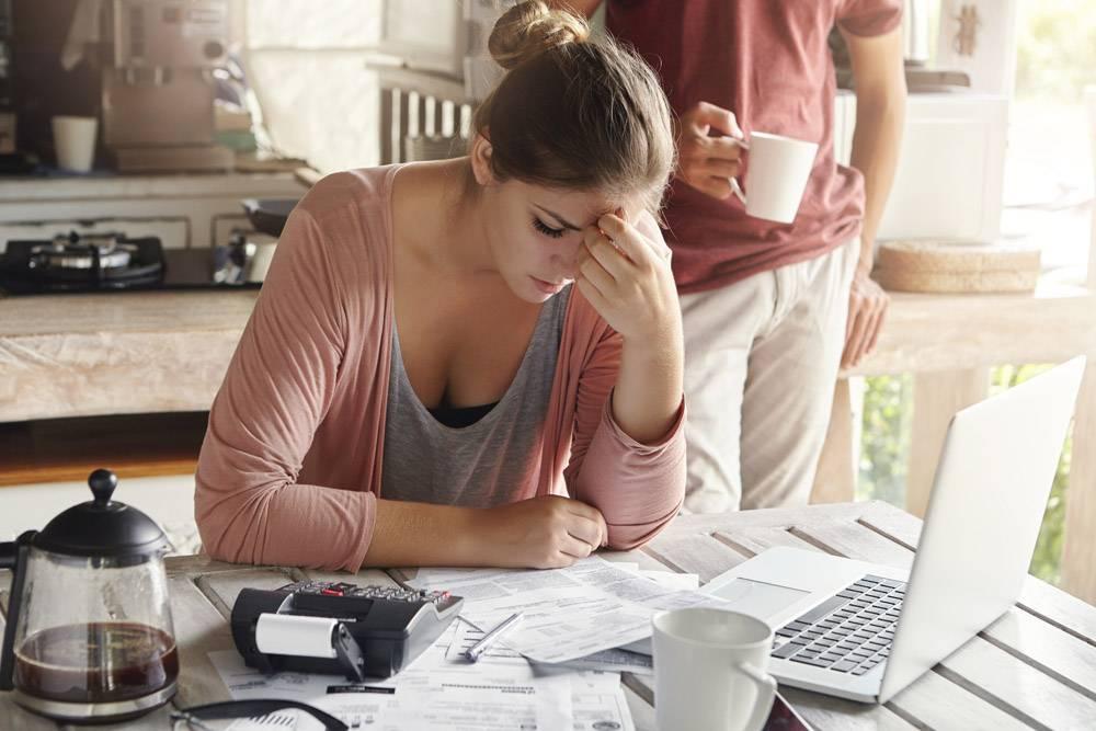 深思熟虑的压力很大的年轻女性坐在厨房的桌_9532744