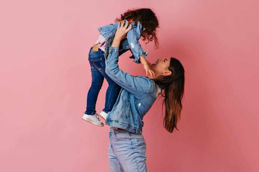 深色头发的年轻女子抱着女儿背景是粉色_12431970