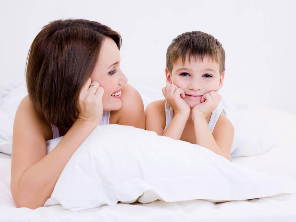漂亮的小孩开心的微笑着的母亲躺在床上_10879406