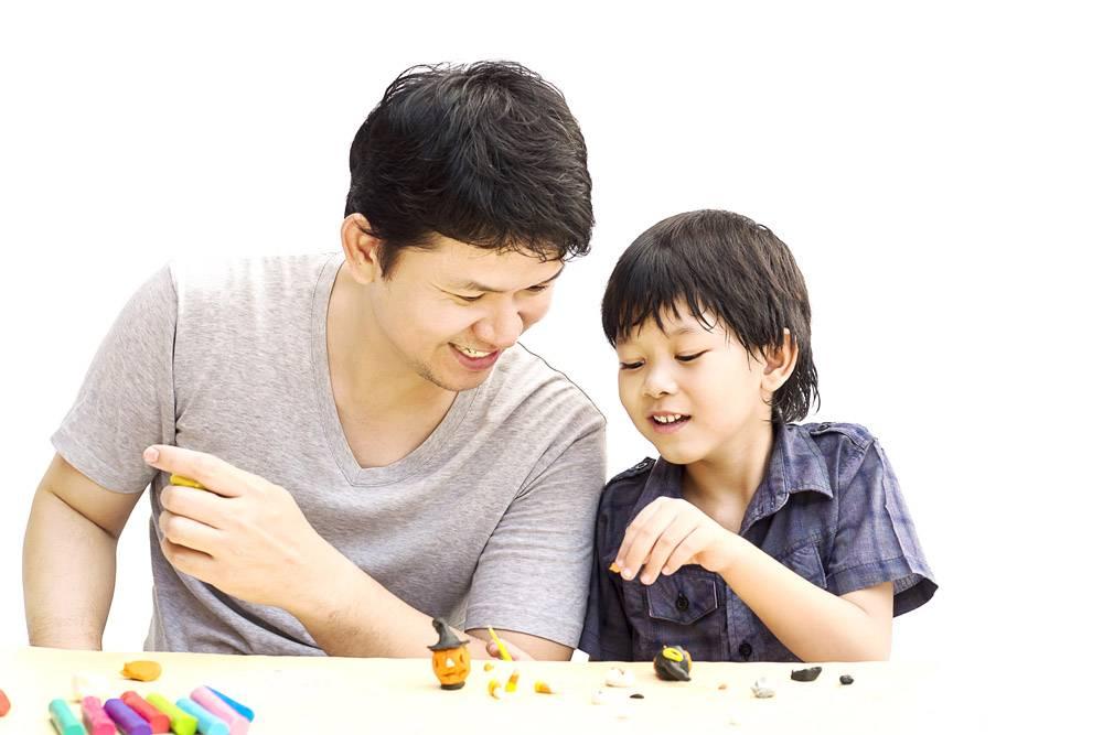 父亲和他的儿子在白色背景上玩万圣节粘土_3763201