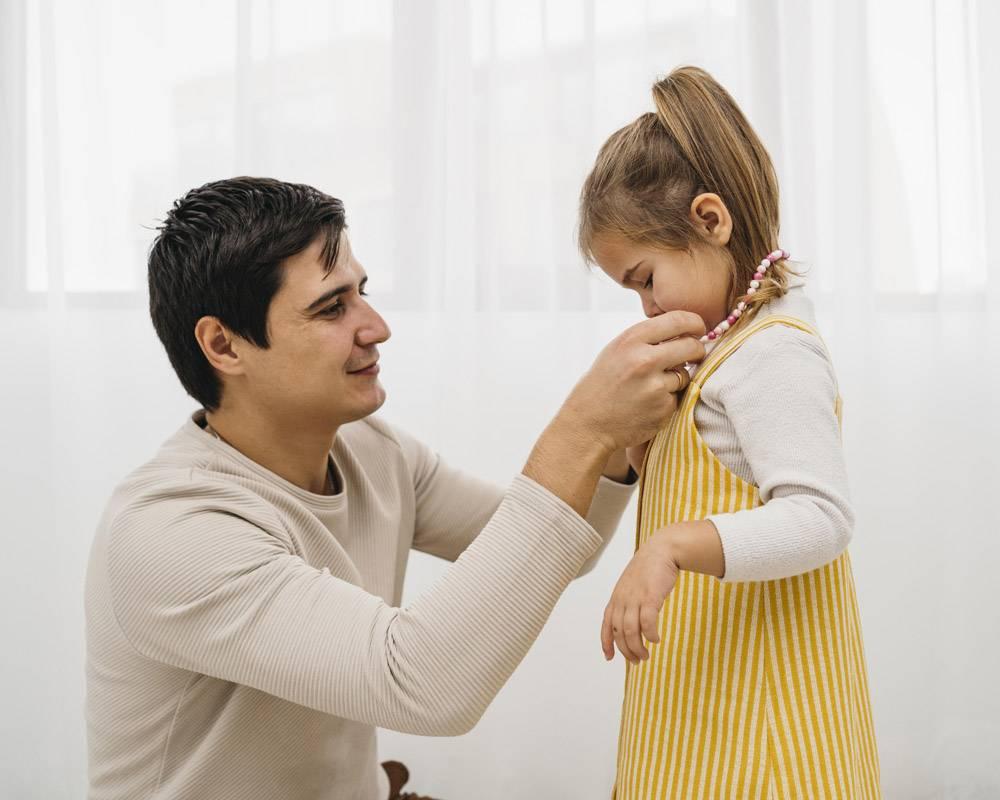 父亲在家里给女儿穿衣服_11904724