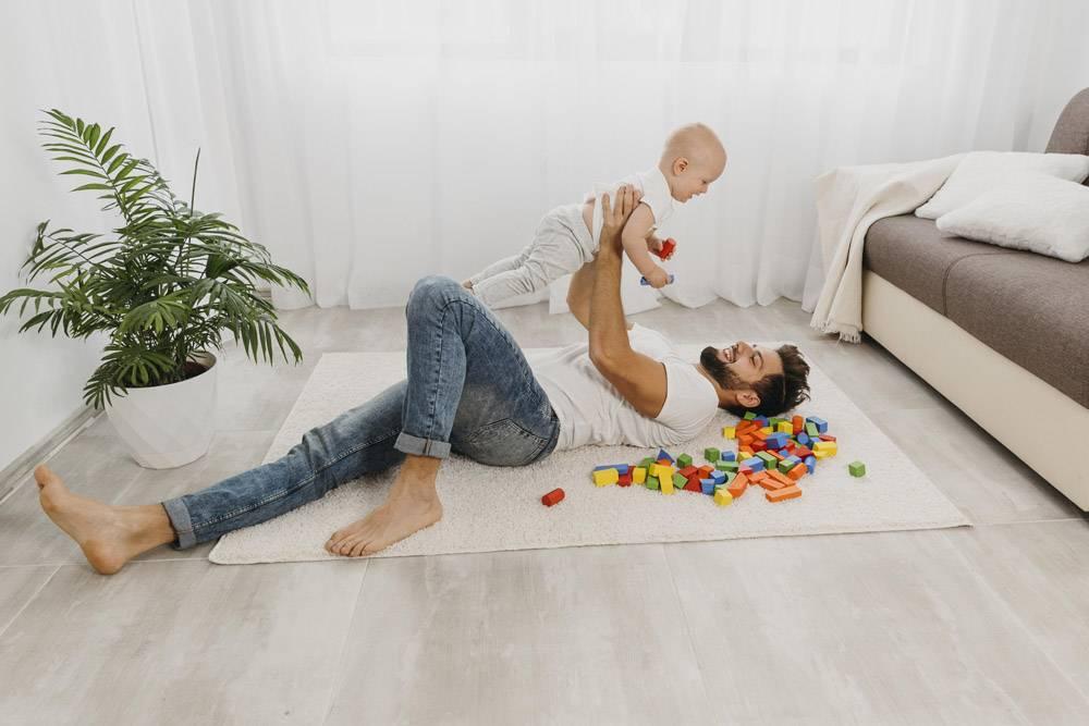 父亲抱着婴儿在地板上玩耍的高角度_11904639