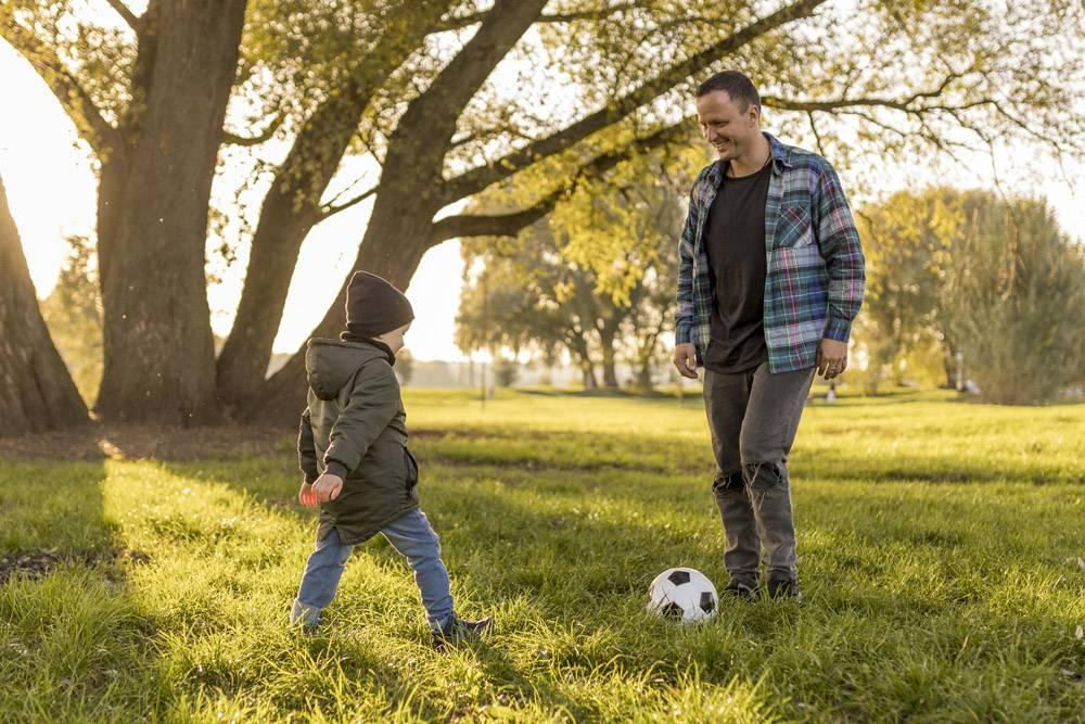 父子俩在公园踢足球_11174609