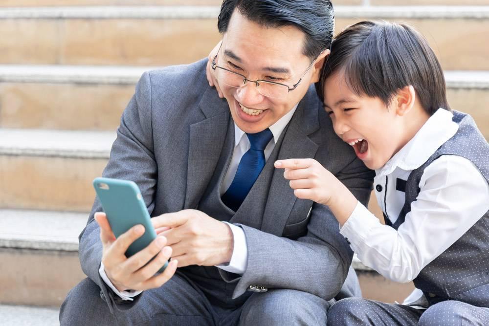 父子俩在商业区城市里一起玩智能手机_11872236
