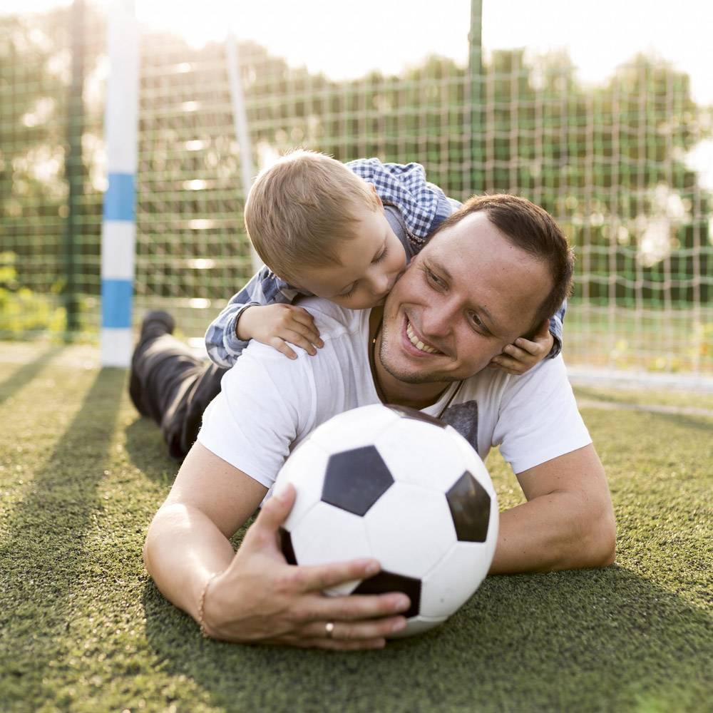父子俩在足球场上休息_11176335