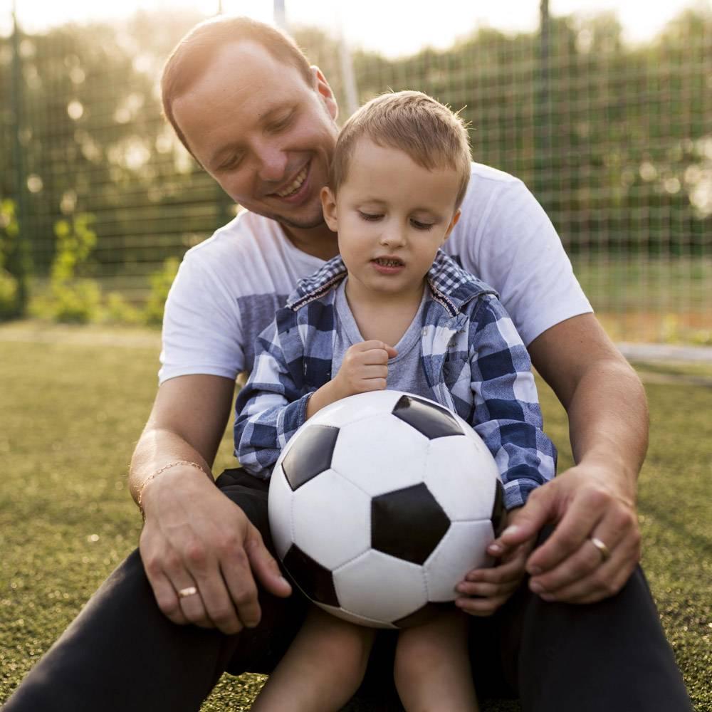 父子俩在足球场上玩耍_11176330