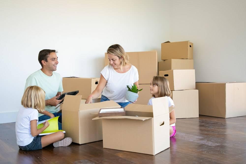 父母和孩子在新公寓里打开东西坐在地板上_11072770