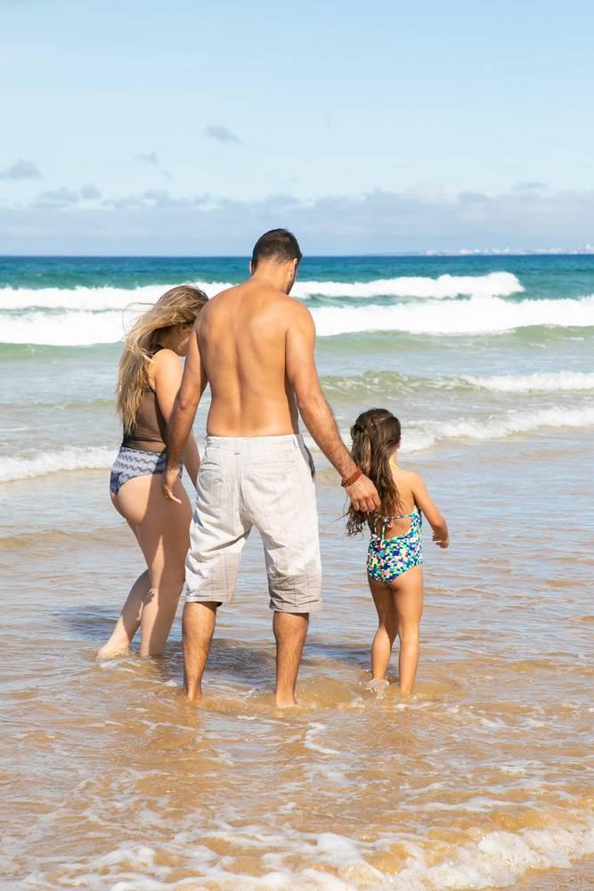 父母和穿着泳衣的小女孩在齐脚踝深的海浪中_11072775