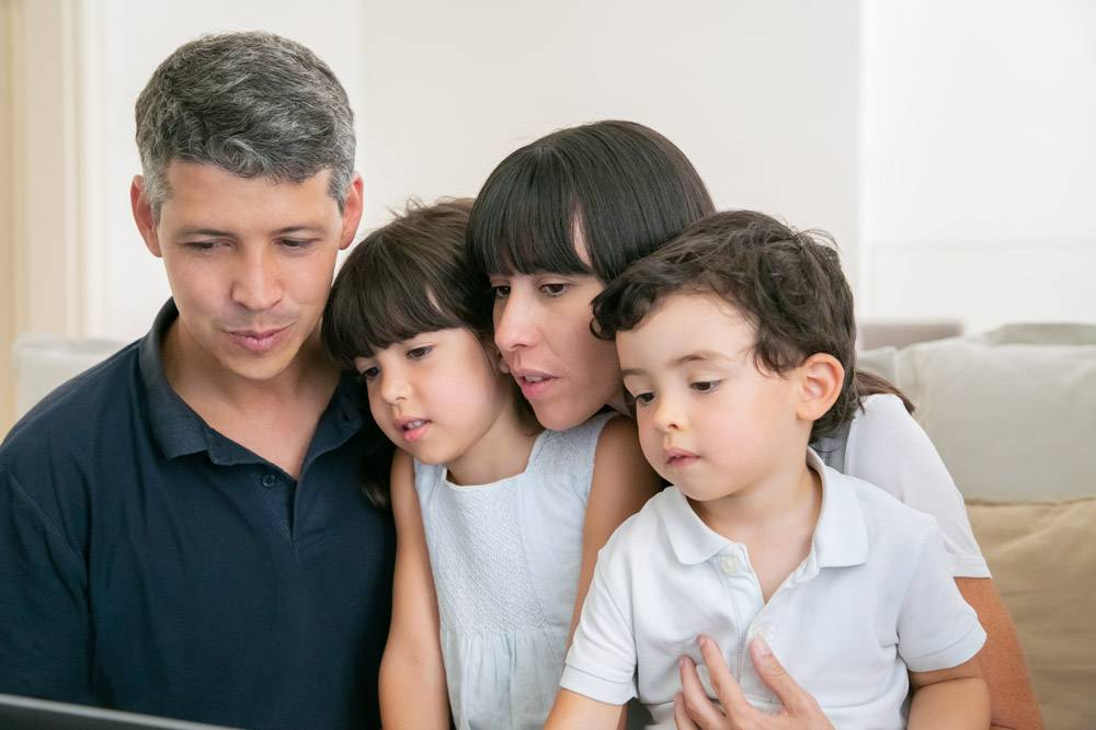 父母夫妇和两个孩子使用电脑进行视频通话_9988591