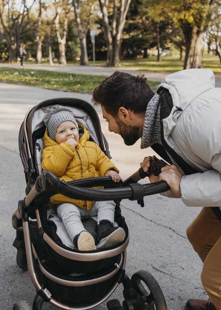 爸爸和孩子坐在外面的婴儿车里_11904683
