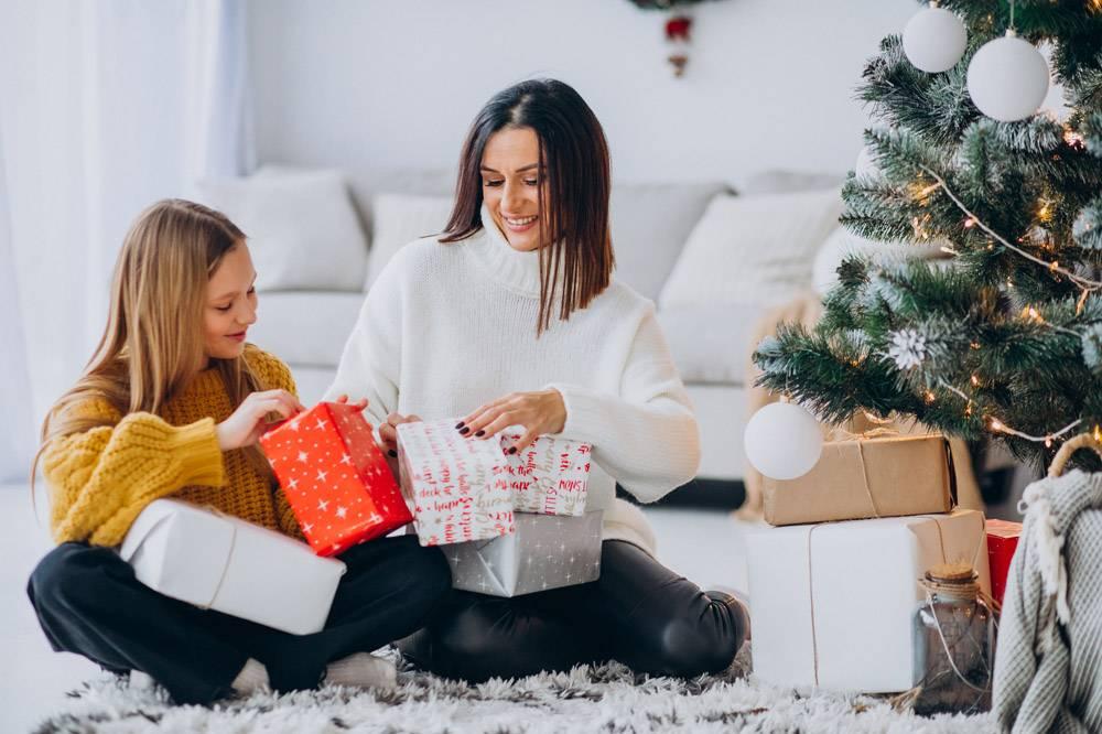 母亲和女儿在圣诞树下打包礼物_12177331