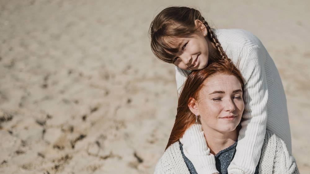 母亲和女孩在海滩上摆姿势_11105717