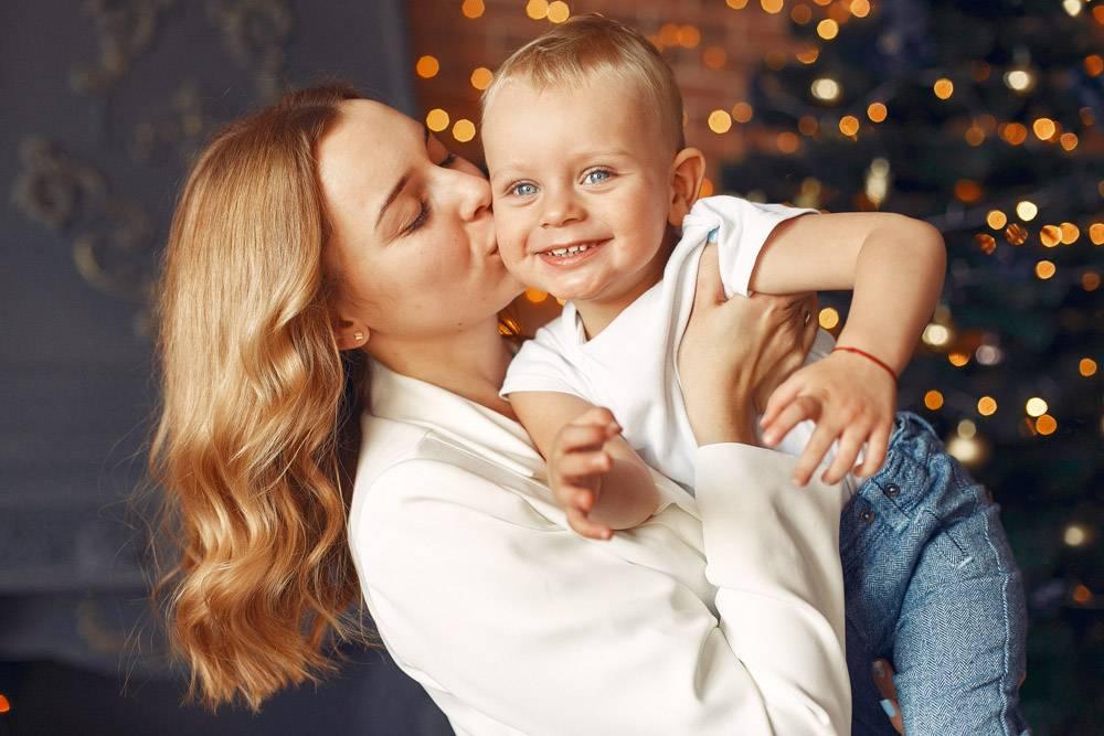 母亲带着可爱的儿子在圣诞树附近的家里_11243361
