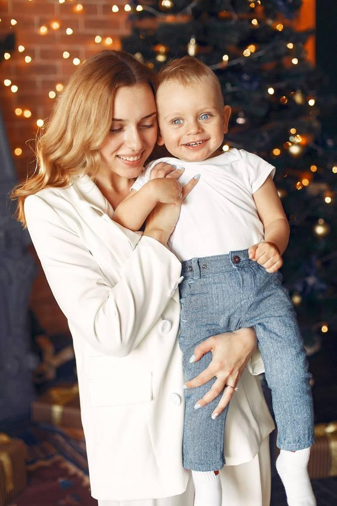 母亲带着可爱的儿子在圣诞树附近的家里_11243365