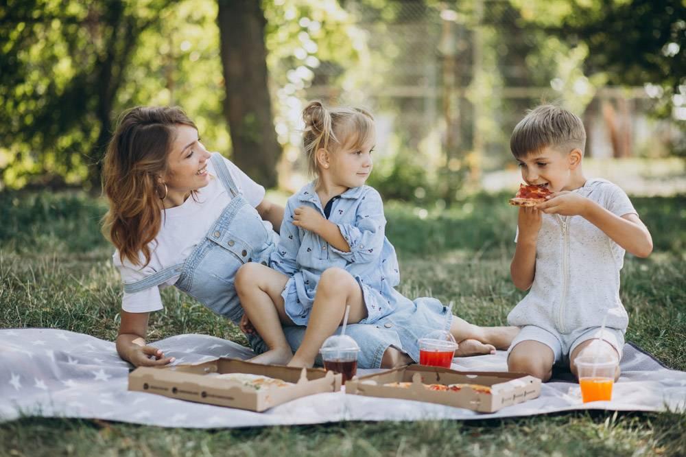 母亲带着儿子和女儿在公园里吃披萨_10298465